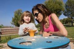 Niño y madre que juegan con la arena en el patio Foto de archivo