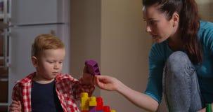 Niño y madre que pasan el tiempo juntos que juega a juegos que se convierten almacen de video