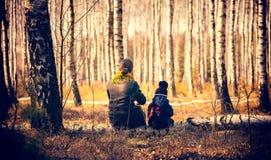 Niño y madre que se sientan en tronco de árbol de abedul en bosque Imagen de archivo libre de regalías