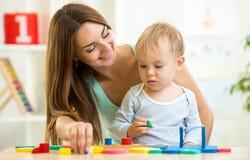Niño y mamá que juegan así como el juguete del rompecabezas Foto de archivo
