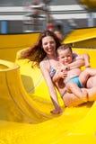 Niño y mamá que juegan con la diapositiva en la piscina Foto de archivo