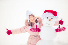 Niño y muñeco de nieve en invierno Foto de archivo libre de regalías