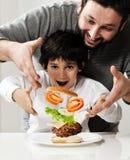 Niño y padre que hacen la hamburguesa Foto de archivo