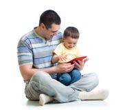 Niño y padre que miran para jugar y para leer la tableta Imágenes de archivo libres de regalías