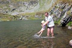 Niño y padre que se refrescan en el lago Fotografía de archivo libre de regalías
