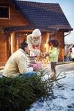 Niño y padres con los regalos delante de la casa de madera Fotos de archivo