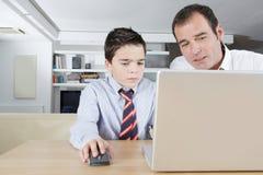 Niño y papá en la computadora portátil Imagen de archivo libre de regalías
