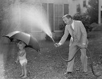 Niño y papá que juegan con la manguera en yarda (todas las personas representadas no son vivas más largo y ningún estado existe G Foto de archivo