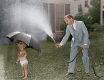 Niño y papá que juegan con la manguera en yarda (todas las personas representadas no son vivas más largo y ningún estado existe G Fotos de archivo