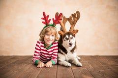 Niño y perro felices el Nochebuena Foto de archivo