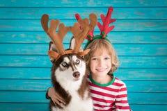 Niño y perro felices el Nochebuena Imagen de archivo libre de regalías