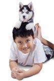 Niño y perro fornido en su cabeza Imagen de archivo