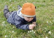 Niño y snowdrops Fotos de archivo
