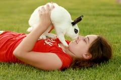 Niño y su animal doméstico Bunny Playing Outdoors Foto de archivo