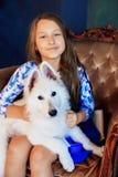 Niño y su perro que se sientan en una silla El concepto de amistad Fotografía de archivo