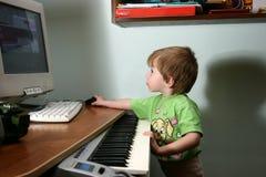Niño y teclado de MIDI fotos de archivo