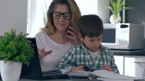 Niño y trabajo, madre de la educación de la cosechadora de la mujer con charla del ordenador sobre el teléfono móvil mientras que almacen de metraje de vídeo