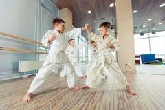 Niños éticos multi jovenes, hermosos, acertados en la posición del karate Foto de archivo