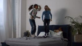 Niños étnicos multi positivos que saltan en la cama metrajes