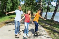 Niños activos que andan en monopatín Fotos de archivo