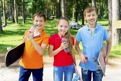 Niños activos que andan en monopatín Imágenes de archivo libres de regalías