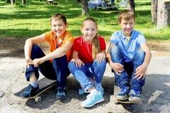 Niños activos que andan en monopatín Imagen de archivo libre de regalías