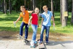 Niños activos que andan en monopatín Foto de archivo
