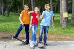 Niños activos que andan en monopatín Imagenes de archivo