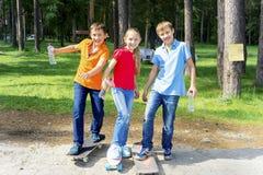 Niños activos que andan en monopatín Fotografía de archivo