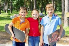 Niños activos que andan en monopatín Imagen de archivo