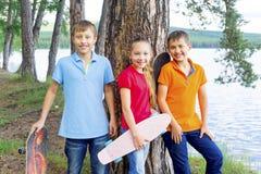 Niños activos que andan en monopatín Fotos de archivo libres de regalías