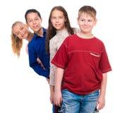 Niños adolescentes divertidos que se colocan uno por uno Fotografía de archivo