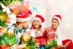 Niños adolescentes lindos que llevan a cabo regalos de Navidad Imagenes de archivo