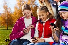 Niños adolescentes ocupados con los teléfonos celulares Foto de archivo libre de regalías