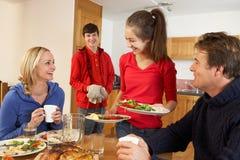 Niños adolescentes provechosos que sirven el alimento a los padres Imagen de archivo
