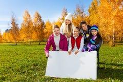 Niños adolescentes que muestran el tablero en blanco del cartel Imagen de archivo libre de regalías