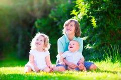 Niños adorables felices en el jardín soleado Imagen de archivo