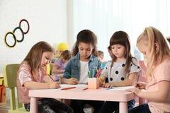 Niños adorables que unen en la tabla Actividades de la hora del recreo de la guardería imagen de archivo libre de regalías