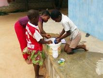 Niños africanos que lavan la ropa Foto de archivo