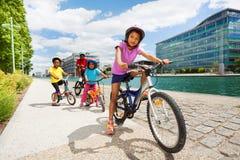 Niños africanos que montan las bicis uno tras otro fotos de archivo libres de regalías