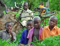 Niños africanos que se sientan en huerto y bici vieja foto de archivo libre de regalías