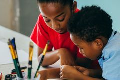 Niños afroamericanos que dibujan y que pintan foto de archivo