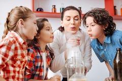 Niños agradables positivos que soplan en el frasco químico Fotografía de archivo libre de regalías