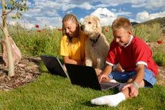 Niños al aire libre con las computadoras portátiles Fotos de archivo