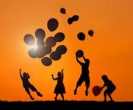 Niños al aire libre que juegan los globos en puesta del sol Fotos de archivo