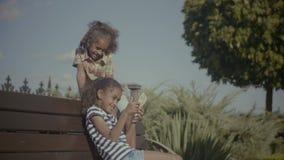 Niños alegres con el teléfono elegante que se sienta en banco almacen de video