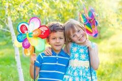 Niños alegres con los molinillos de viento Fotografía de archivo libre de regalías