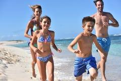 Niños alegres con los padres que corren en la playa Fotografía de archivo
