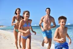 Niños alegres con los padres que corren en la playa Imagen de archivo libre de regalías
