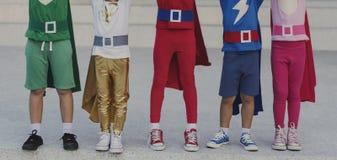 Niños alegres de los super héroes que expresan concepto de la positividad foto de archivo